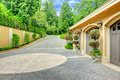 Luxury house view of garage and driveway beautiful with three car pots with trees trimmed hedges Royalty Free Stock Images