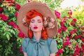 Luxury retro girl with red lips in mint dress on a beautiful flower summer background. Young redhead model in a hat with flowers Royalty Free Stock Photo