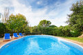 Luxury summer swimming pool with sun loungers for relaxation and Stock Image