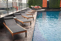 Luxury swimming pool with long chairs or benches Stock Photo