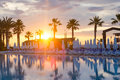 Luxury swimming pool sunrise over with palm trees and sunbeds Royalty Free Stock Images
