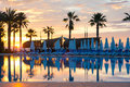 Luxury swimming pool sunrise over with palm trees and sunbeds Royalty Free Stock Image
