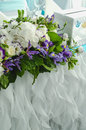 Luxury table beautiful, rich decoration with lush leaves, white hydrangea, delicate cream roses, purple eustoma, blue Royalty Free Stock Photo