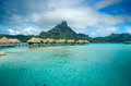 Luxury thatched roof bungalow resort on bora bora overwater in a vacation in the clear blue lagoon with a view the tropical island Royalty Free Stock Image