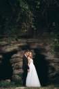 Luxury wedding couple hugging and kissing on the background gorgeous plants and cave near ancient castle Royalty Free Stock Photo