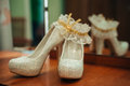 Luxury wedding elegant bridal shoes and white garter on background Royalty Free Stock Images