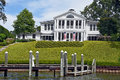 Luxury white house with boat dock on river Royalty Free Stock Photo
