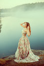 Luxury woman in a forest in a long vintage dress near the lake. Royalty Free Stock Photo