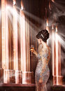 Luxury young woman in evening dress with glass of champagne standing at the window in sunshine chic female silver posing Royalty Free Stock Image