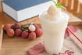Lychee fruity frappe in a glass with fresh lychees behind Stock Photography