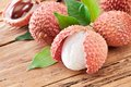 Lychee with leaves on a wooden table Royalty Free Stock Images