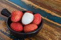 Lychee on a wooden table in black bowl Stock Image