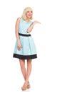 Lycklig härlig flicka i ljus blå färgklänning som framlägger produkten Arkivfoto