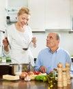 Lycklig mogen kvinnamatlagning med maken i kök Royaltyfri Foto