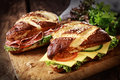 Lye bread rolls with cheese and salami a german bavarian speciality glazed baked fresh lettuce tomato Stock Photo