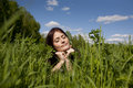Lying in grass enjoying sun an attractive young woman warmth of on her face while a field of long and weeds Stock Image