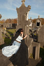 Lying on a tombstone young woman in victorian dress Royalty Free Stock Photo
