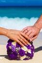 Mãos masculinas e fêmeas com o ramalhete o de encontro do casamento das alianças de casamento Fotos de Stock