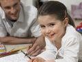 Mädchen mit vater coloring book on boden Lizenzfreies Stockfoto
