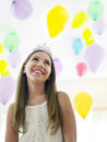 Mädchen in tiara looking up against balloons Lizenzfreie Stockfotografie