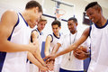 Männlicher highschool basketball team having team talk with trainer Lizenzfreies Stockfoto