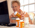 Médecine de commande de femme aîné en ligne Photo stock