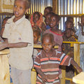 Maasai school children sitting on wooden benches in a tin building in the village of http www association org html Stock Photo
