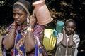 Maasai woman and child carrying drinking water keya masai mara rift valley village entesekera young a girl have fetched in a small Royalty Free Stock Photos