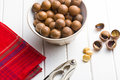 Macadamia nuts in bowl on white wooden table Royalty Free Stock Photography