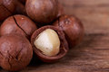 Macadamia nuts brown seed on wooden background Royalty Free Stock Images