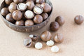 Macadamia nuts in coconut bowl on brown background Royalty Free Stock Photos