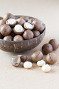 Macadamia nuts in coconut bowl on corkwood background Royalty Free Stock Images