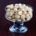 Macadamia nuts in the dessert bowl on brown background Royalty Free Stock Image