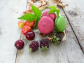 Macaron french macarons with blackberries and cherries on an old wooden table Stock Photography