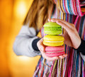 Macaron young woman holding the french pastry in cafe Stock Photos