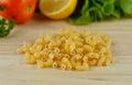 Macaroni pasta close up on wooden background Royalty Free Stock Photo
