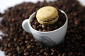 Macarons and coffee beans beige macaron in a cup full of background Stock Photos