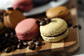 Macarons and coffee beans some on a wooden trencher Royalty Free Stock Photography