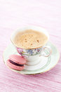 Macaroon pink on a saucer with cup of coffee Stock Image