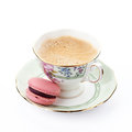 Macaroon pink on a saucer with cup of coffee Stock Photos