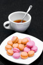 Macaroon and tea pile of pink orange in a plate with a cup of on black table Stock Images