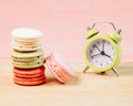 Macaroons and alarm clock on table, vintage stylized photo Royalty Free Stock Photo