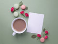 Macaroons, coffee and rose on green background. Top view. Flat lay Royalty Free Stock Photo