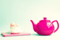 Macaroons in a cup over book and red teapot pink tea checkered Royalty Free Stock Photo