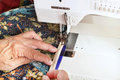 Machine binding a quilt quilter guides material through the walking foot of sewing Royalty Free Stock Photography