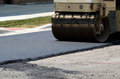 A machine used to flatten and smooth hot asphalt is smoothing out a new road Royalty Free Stock Image