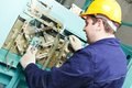 Machinist with spanner adjusting lift mechanism Royalty Free Stock Photo