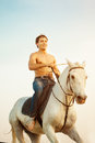 Macho man and horse on the background of sky and water. Boy mode Royalty Free Stock Photo