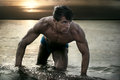 Macho young handsome muscular man posing in water on sea beach against sunset at night Royalty Free Stock Images