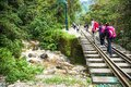 People cross the railway bridge over a stream that flows into Urubamba River near to  Machu Picchu Pueblo or Aguas Calientes town Royalty Free Stock Photo